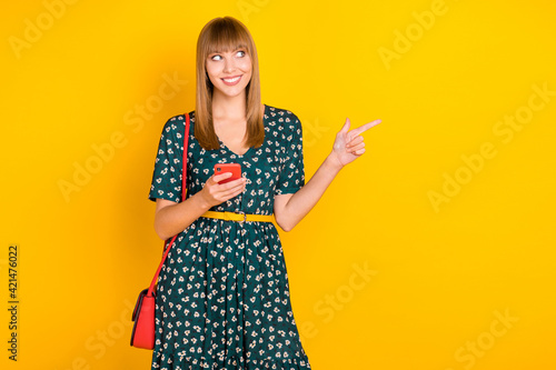 Portrait of attractive cheerful girl using gadget demonstrating ad like follow copy space isolated over bright yellow color background