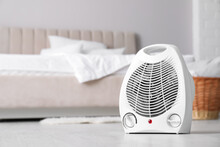 Modern Electric Fan Heater On Floor In Light Bedroom. Space For Text