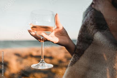 Bella ragazza tiene in mano un calice di vino bianco sulla spiaggia Fototapete
