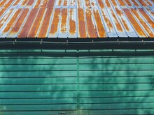 Rusted Roof And Green Wood