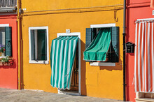 Colorful Houses And Doors With Curtain In Burano, A Little Town Full Of Canals Near Venice, Italy.