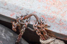 Close-up Of Rusty Chain Tied Up On Metal Wall