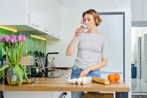 Photo Beautiful young woman drinks water before making breakfast