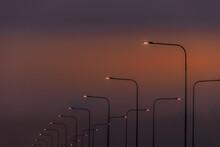 Street Lights Against Orange Sky