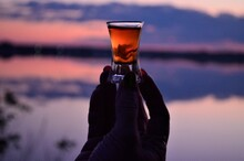 Added A Female Hand Holding A Cognac Glass Against The Sky During Sunset On The River