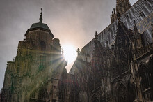 Cinematic View Of St. Stephen's Cathedral In Downtown Of Vienna, Austria. Rays Of Sun Between Towers And Tops Of Church. Bright Sunny Sky. Medieval Roman Catholic Place Of Worship. Scenic Panoramic.