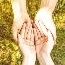 Close-up Of People Holding Hands On Field