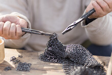 Midsection Of Man Working On Chain Mail Armor At Table