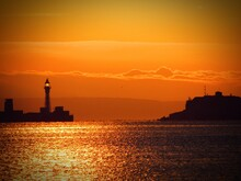 Silhouette Lighthouse By Sea Against Orange Sky