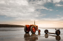 Red Tractor On The Beach At Sunset