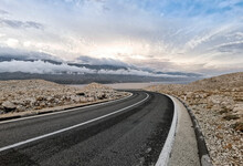Empty Road With With Dividing Line. Rocky Terrain, Beautiful Sky.