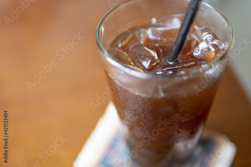 Closeup shot of a glass of cold coffee with ice on the table Fototapet