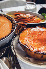 Pie And Baked Pumpkin Setting Table On Thanksgiving Day Celebration Dinner On Rustic Table