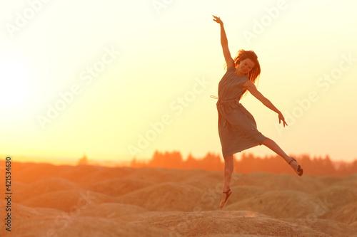 Papel de parede Elegant woman with long hair in long dress dancing elegant on sand in desert