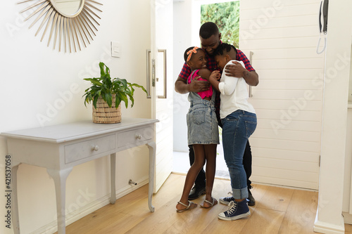 Happy african american father hugging son and daughter in hallway of home Fotobehang