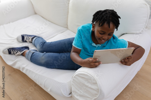Smiling african american boy with short dreadlocks lying on couch using digital tablet