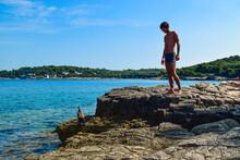 Silhouette Of A Young Guy On A Rocky Ambrela Beach Near The Wild Cormorant Bird On The Background Of The Adriatic Sea. Pula. Croatia.