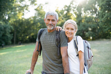 Portrait Of Smiling Mature Couple Standing In Forest