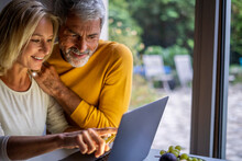 Smiling Mature Couple Making Online Payment With Credit Card