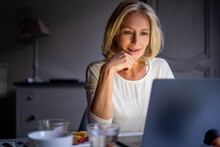Smiling Mature Woman Using Laptop At Home