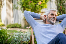 Smiling Mature Man With Hands Behind Head Sitting On Deckchair