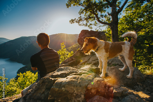 Canvas Print Man relaxing with his dog at a beautiful viewpoint with rocks and lake