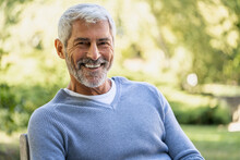 Portrait Of Smiling Mature Man Sitting On Chair
