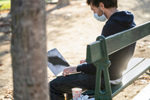 Man Wearing Protective Face Mask Using Laptop In Public Park