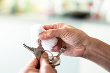 Close-up Of Woman's Hands Disinfecting Keys With Wet Wipe At Home