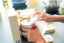 Close-up Of Woman's Hands Disinfecting Groceries With Wet Wipe At Home