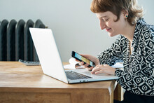 Smiling Woman Using Smartphone And Laptop While Working From Home