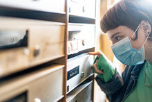 Woman Wearing Protective Face Mask Looking Through Drawers In Locker Room