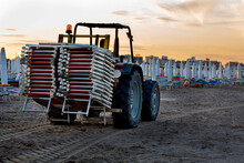 The Tractor Carries The Sun Loungers Removed From The Beach In The Evening