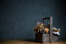 Composition Of Dried Flowers In A Wooden Basket On Dark Background