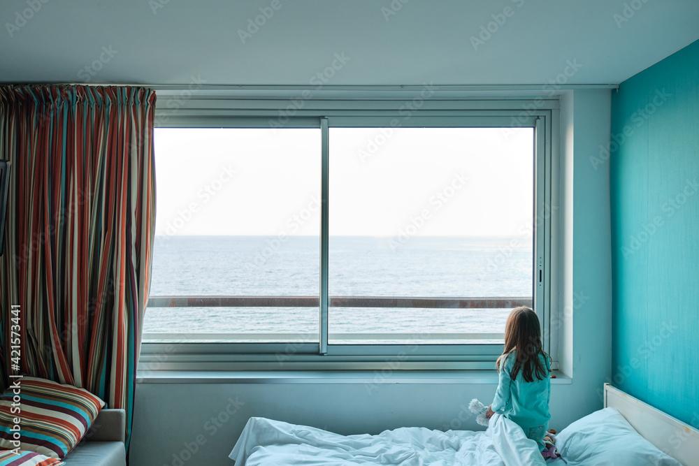 Obraz Une petite fille regarde la mer à travers la fenêtre d'une chambre d'hôtel fototapeta, plakat