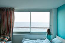 Une Petite Fille Regarde La Mer à Travers La Fenêtre D'une Chambre D'hôtel