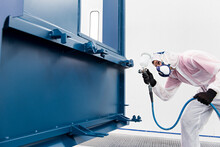 Worker Painting Railroad Car With Blue Dye