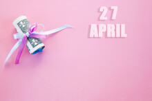 Calendar Date On Pink Background With Rolled Up Dollar Bills Pinned By Pink And Blue Ribbon With Copy Space. April 27 Is The Twenty-seventh Day Of The Month
