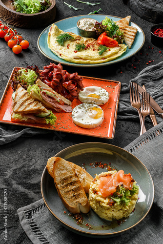 Fototapeta Variety of delicious breakfast dishes with eggs, vegetables, salad leaves, sausages, toast served on plates over dark background, close up. Healthy breakfast concept obraz