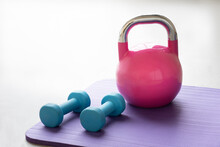 Close Up Of A Blue Light Dumbbells On A Violet Yoga Pilates Mat On The Floor Of A Gym With A Pink And Silver Kettlebell. Horizontal