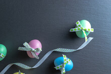 Easter Flat. Colorful Egg With Tape Ribbon On Dark Rough Stone Background In Happy Easter Decoration. Spring Holiday Top View Concept.