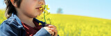 Little boy smells rapeseed flower