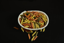 Closeup Shot Of Tri-color Noodles On An Oval Banneton On An Isolated Background