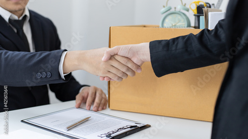 Obraz na plátně Young woman wearing a black suit raises a brown cardboard box from the office, Businessmen pack personal belongings and equipment after Resign or being fired, Employment contract is expire