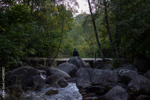 Joven sentado en unas rocas rodeado de bosque con un pequeño puente de madera.