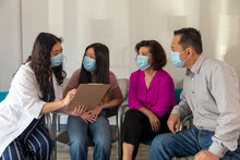 Doctor Explains Form To Asian Family In Waiting Room