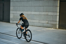 Rear View Of Professional Female Cyclist In Black Cycling Garment And Protective Gear Riding Bicycle In City, Passing Buildings While Training Outdoors On A Daytime