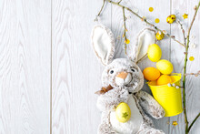 Yellow And Orange Easter Painted Chicken Eggs In Decor Bucket With Rabbit Bunny Toy, Willow Branches, Spring, Easter Concept On Wooden Background. Christian Orthodox Holiday