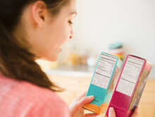 Woman Reading Nutrition Facts On Food Packaging