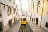Fototapeta Uliczki - Trams in Lisbon city. Famous retro yellow funicular tram on narrow streets of Lisbon old town on a sunny summer day. Tourist attraction